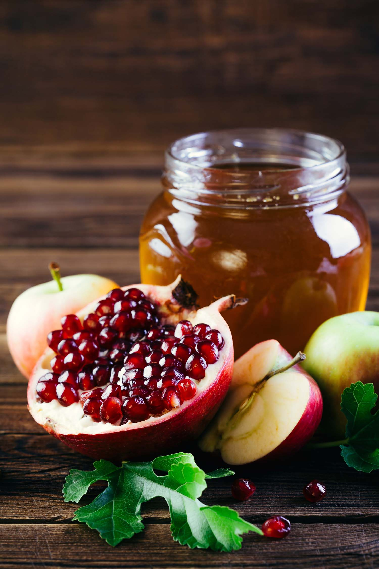 Rosh Hashanah table with honey, apple and pomegranate.