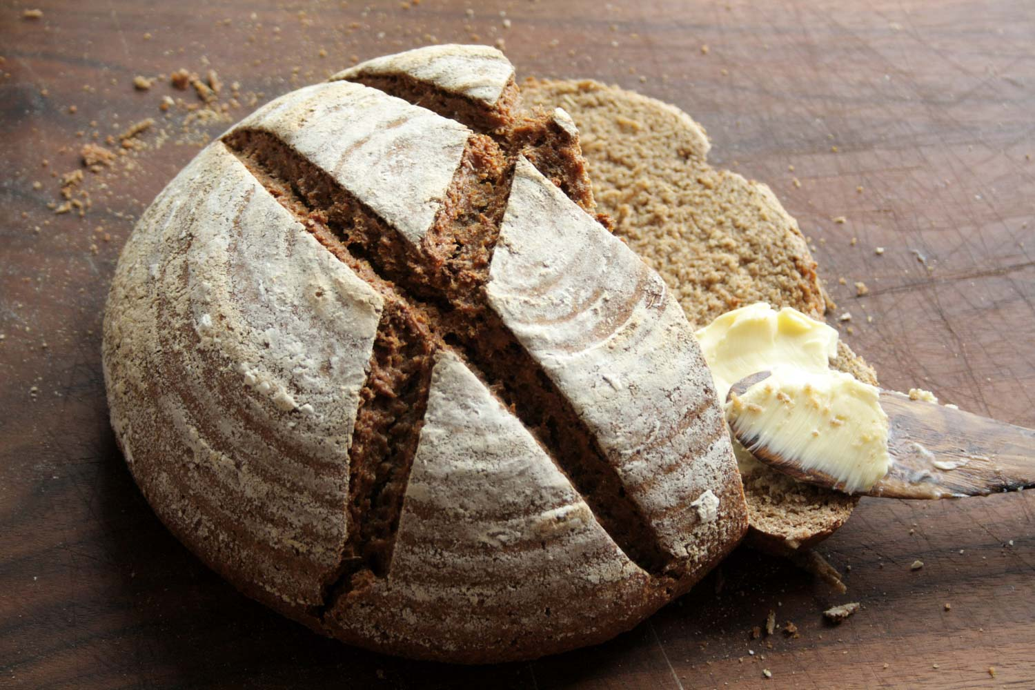 Handmade rye bread with butter on a wooden background