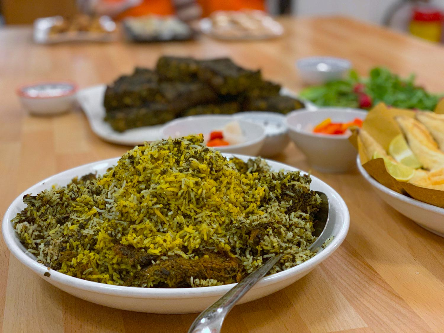 Sabzi polo a traditional Nowruz food rice dish in a white bowl on a table with other food.
