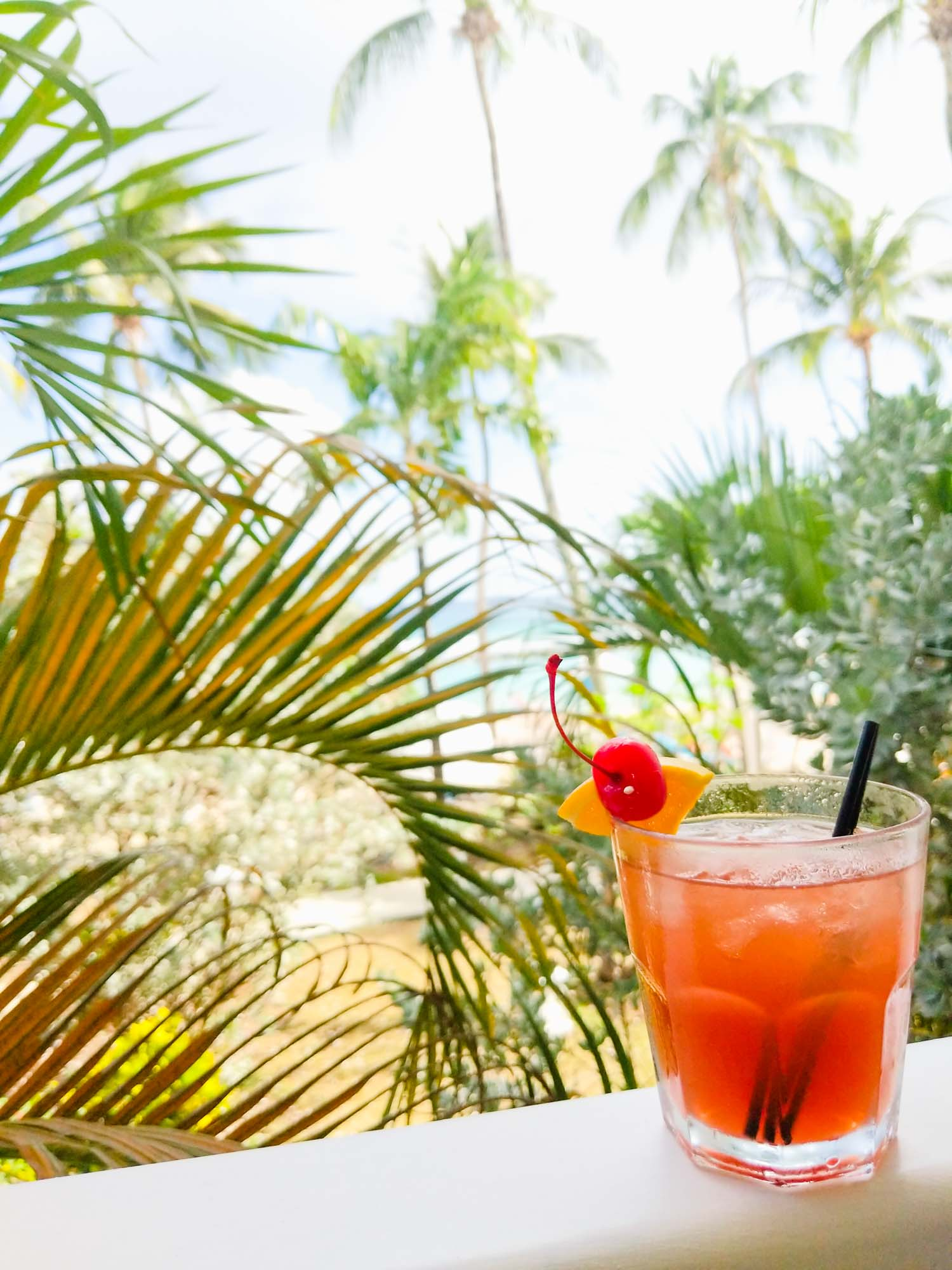 Jamaican rum punch, one of the most popular drinks in Jamaica, on a railing with palm trees in the back.
