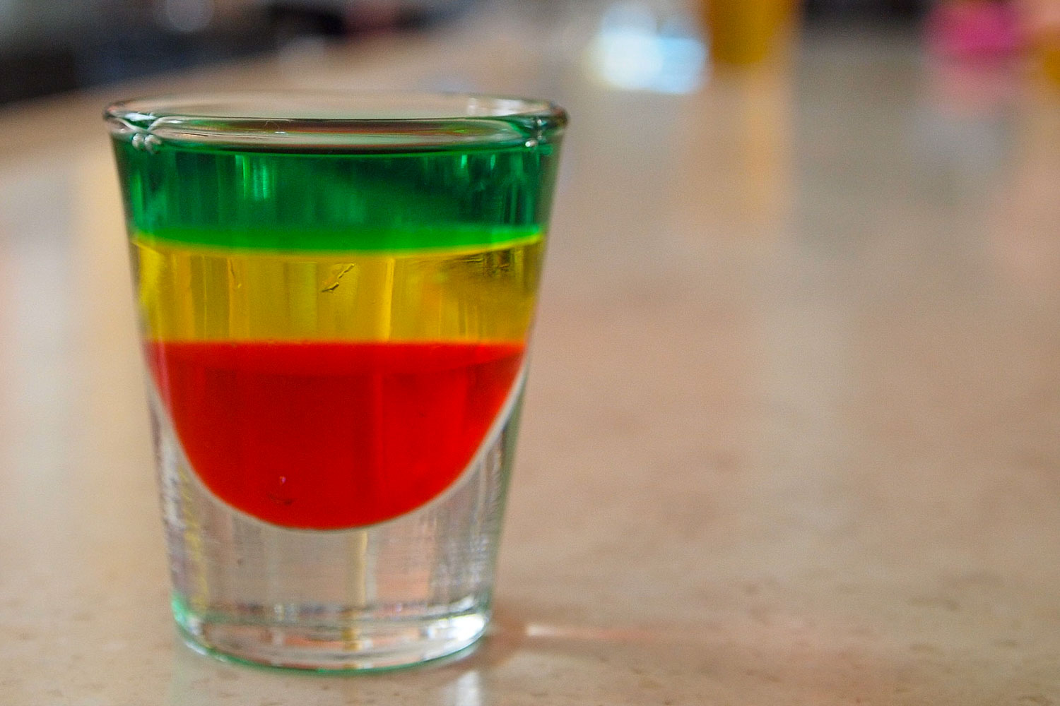 Jamaican cocktail called the Bob Marley shot, which is red, yellow and green on a bar.