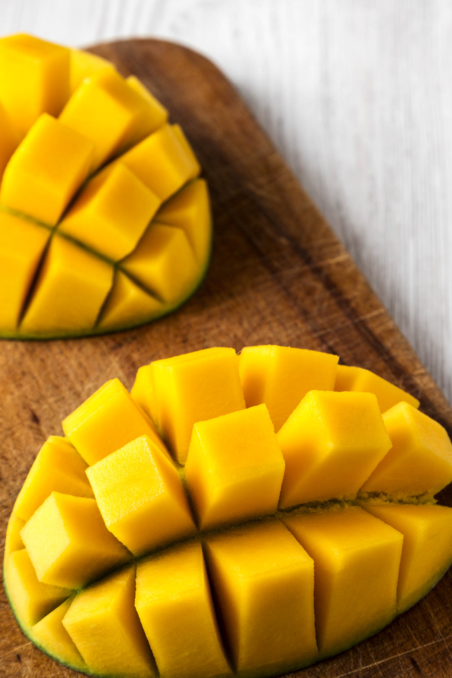 Jamaican mango fruit cut up and ready to eat, rustic wooden board on a white wooden table