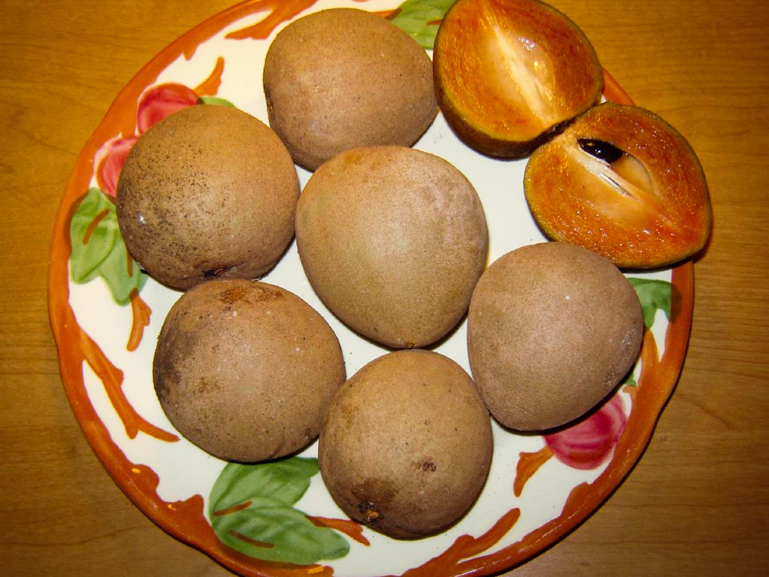 Jamaican naseberry fruis on a plate with one cut to show inner flesh