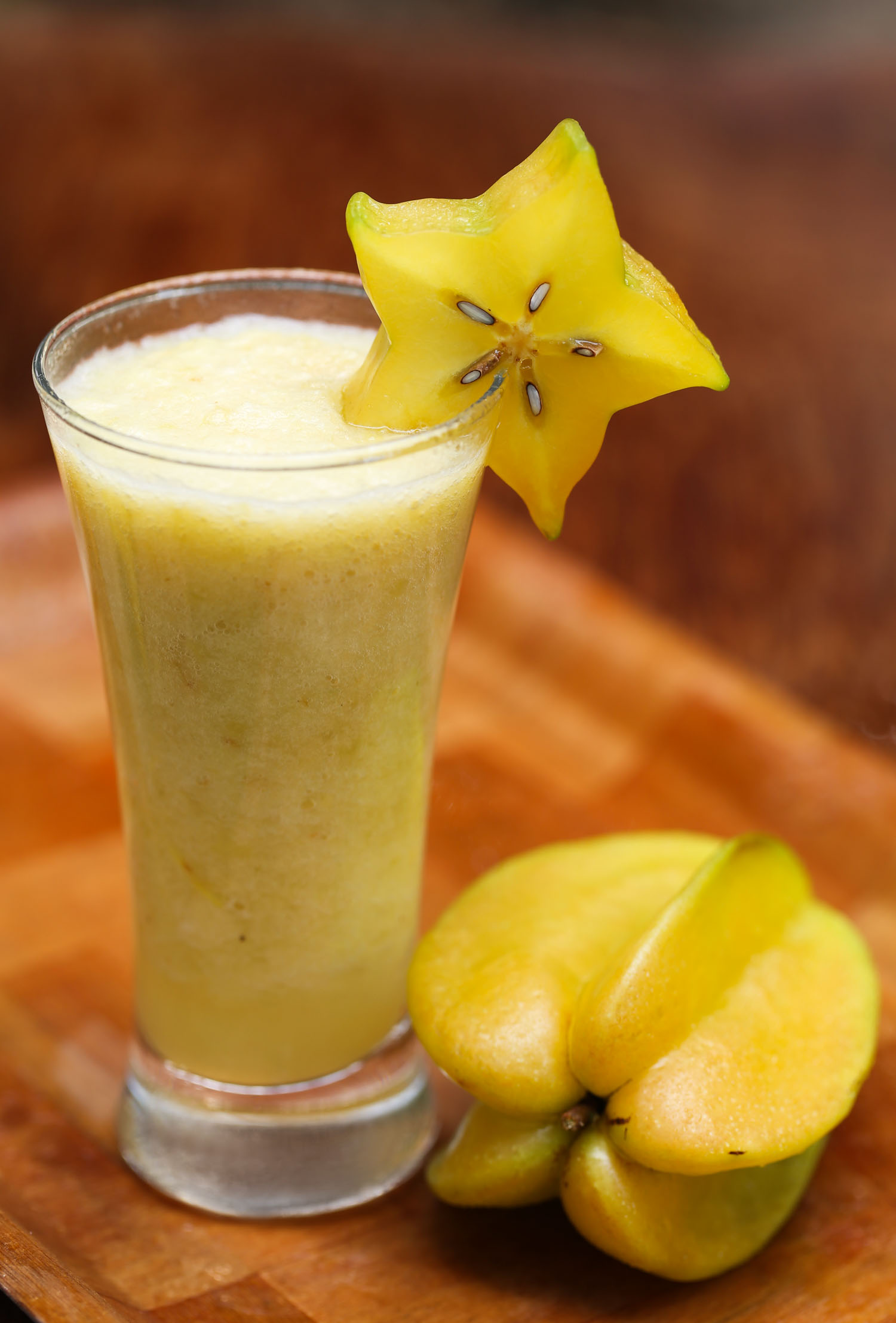 Kamranga also known as Carambola or starfruit juice in a glass with ripe fruit