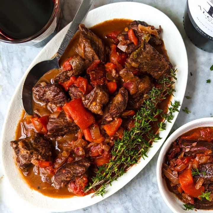 Spanish beef stew on a white plate with a spoon.