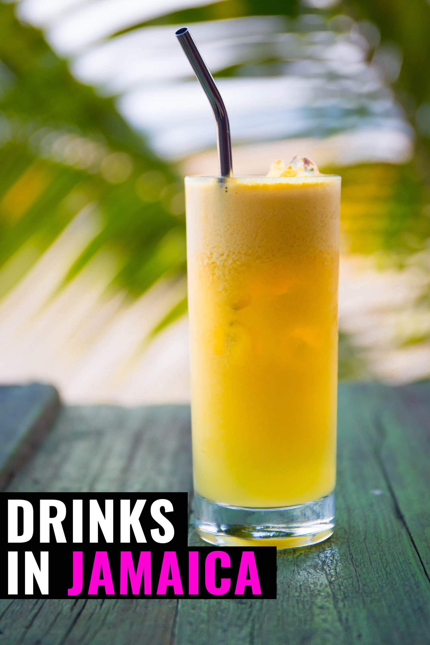 Tropical Jamaican drink on a table with palm trees in the back