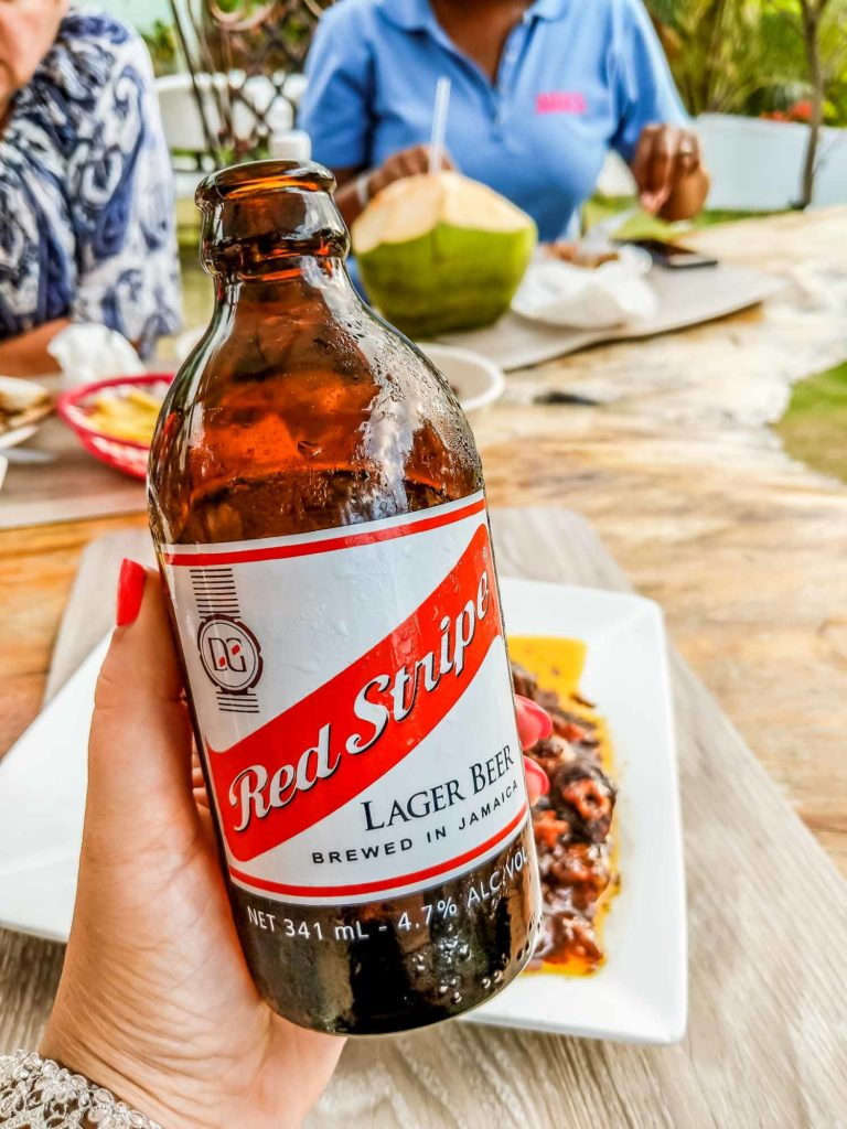 Red Stripe beer, popular drinks in Jamaica in a woman's hand