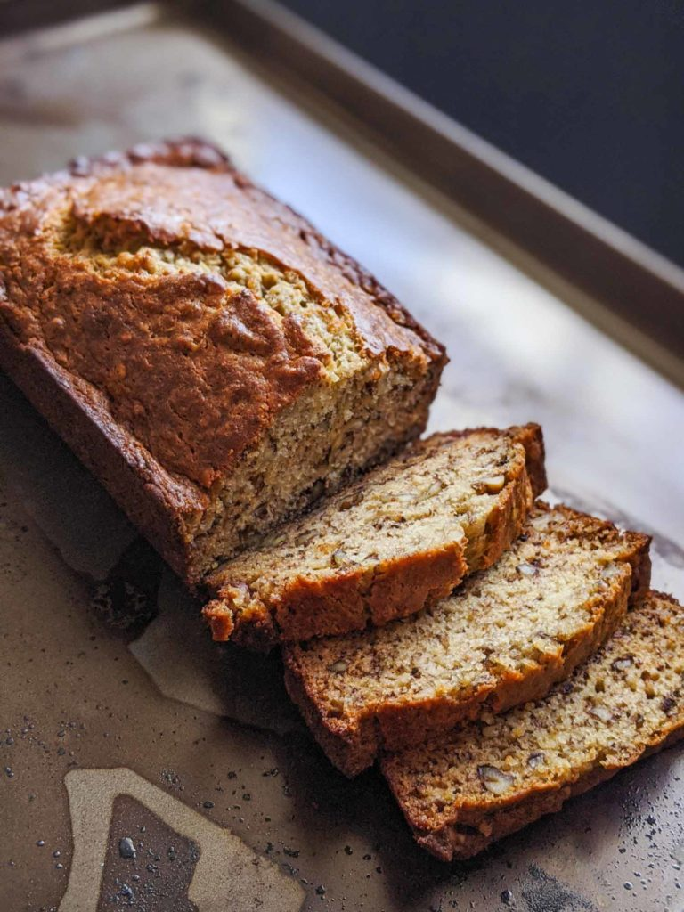 Homemade banana bread sliced on a dark background