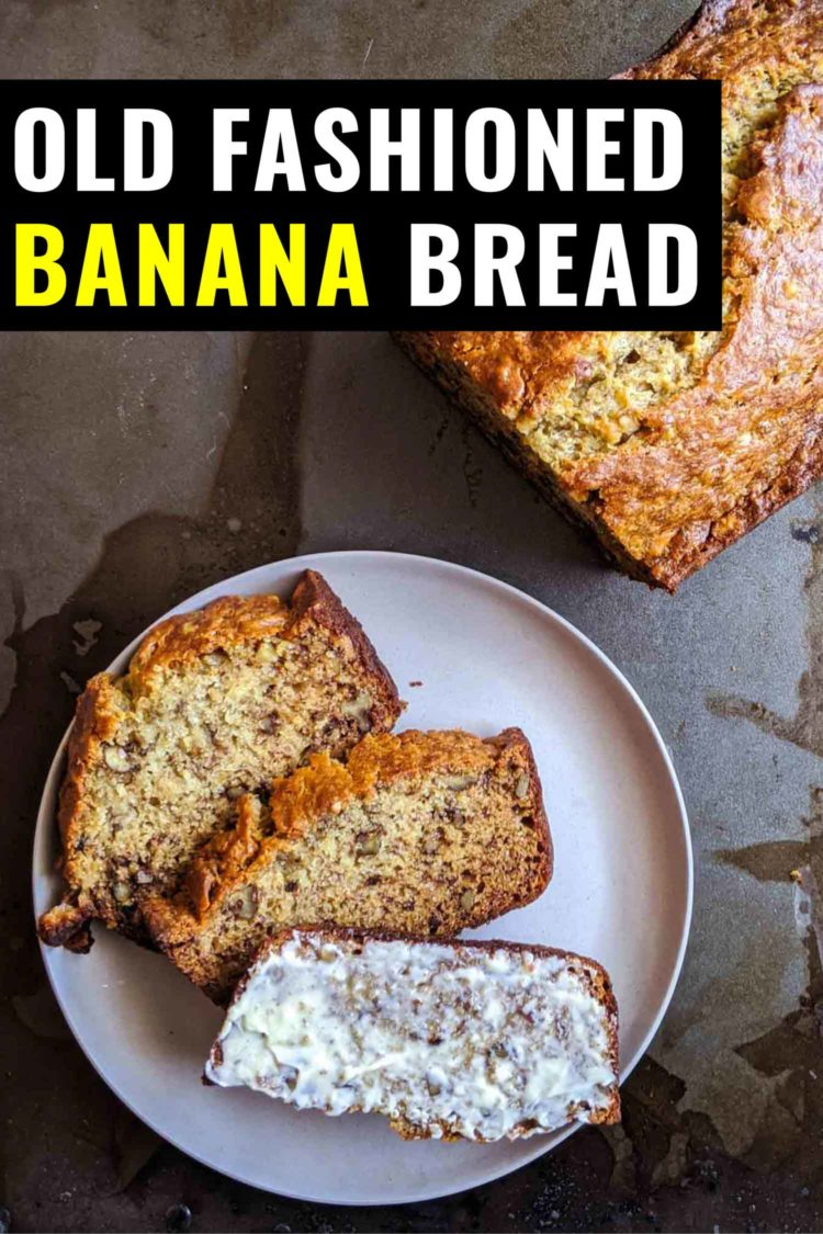 Old fashioned banana bread on a tray, one slice is buttered