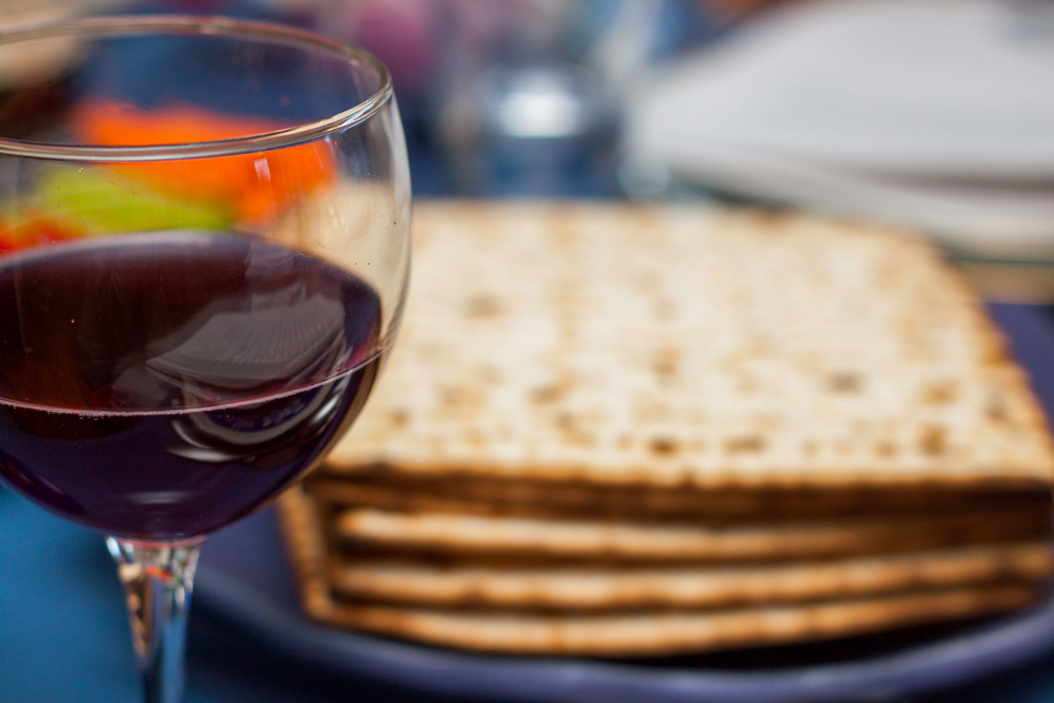 Passover seder wine with matzoh crackers in the background.