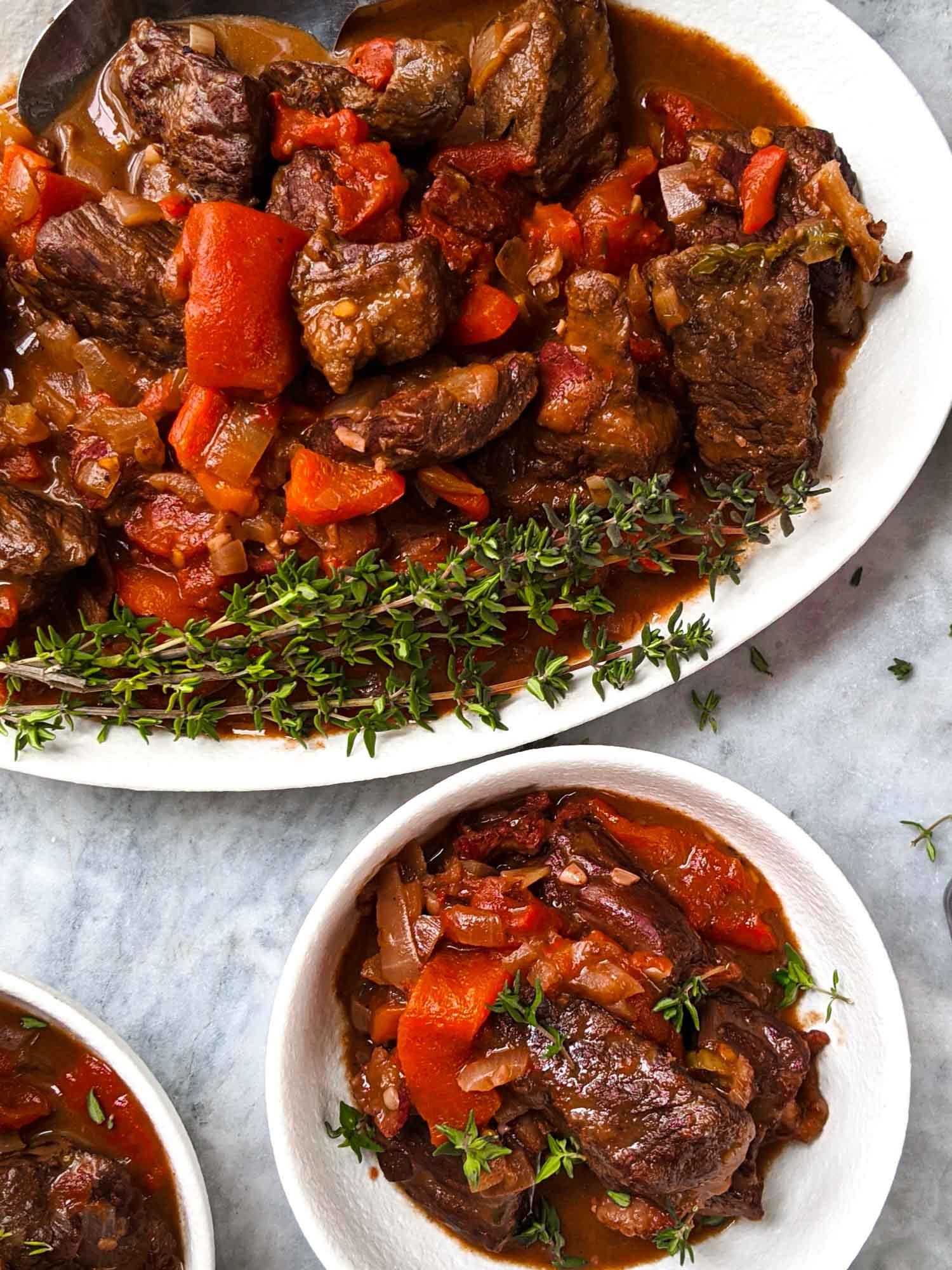 Red wine Spanish stew on white plates in a marble background