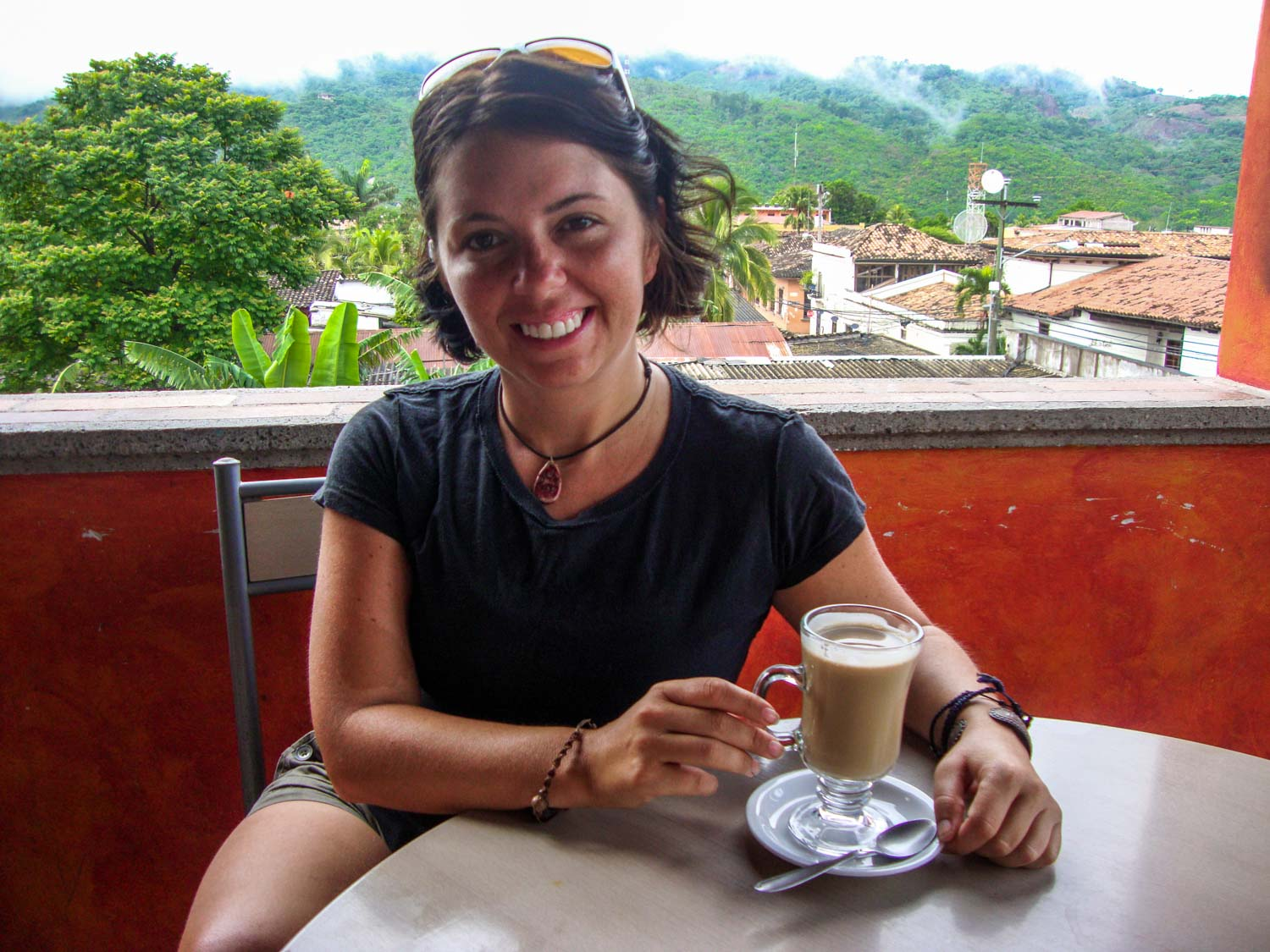Ayngelina at a table with coffee, views of Copan Honduras in the background