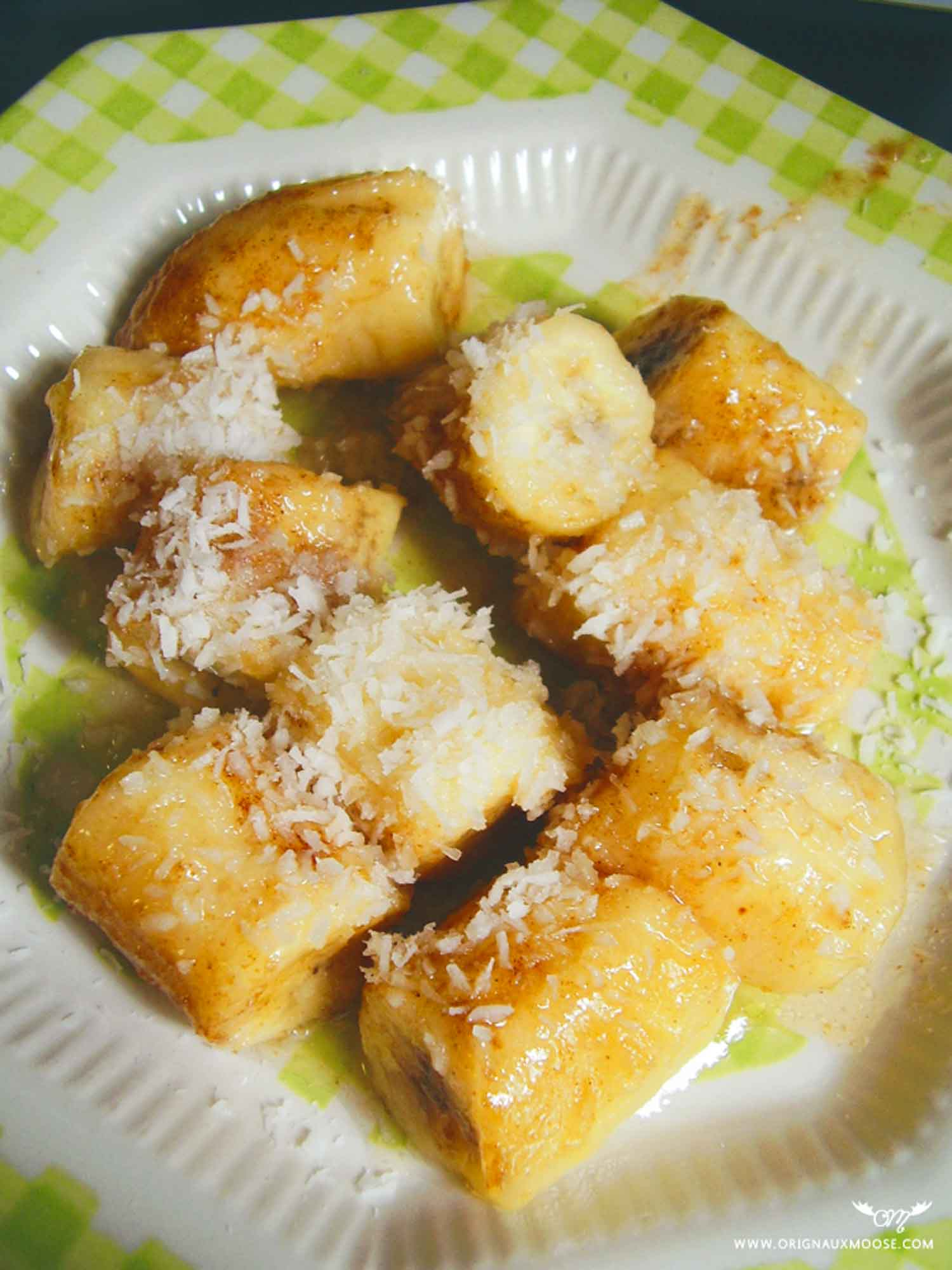 Baked bananas with coconut topping on a green and white plate.