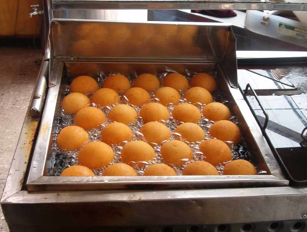 Bunuelos in Honduras lined up in a commercial fryer