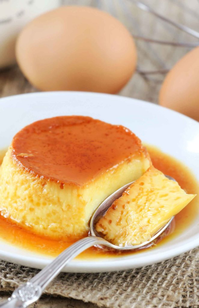 Flan that has been cut into with a spoon on a white plate with eggs in the background.