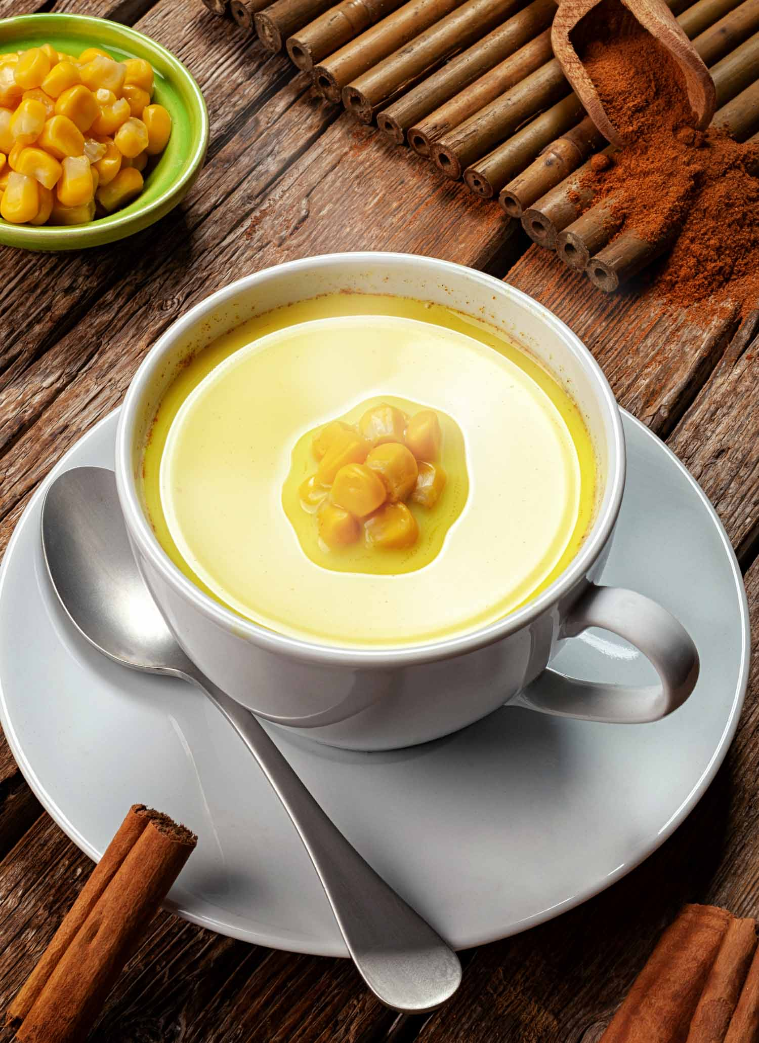 Atol de elote, one of the most common Honduran drinks, on a table with corn and cinnamon garnishes.