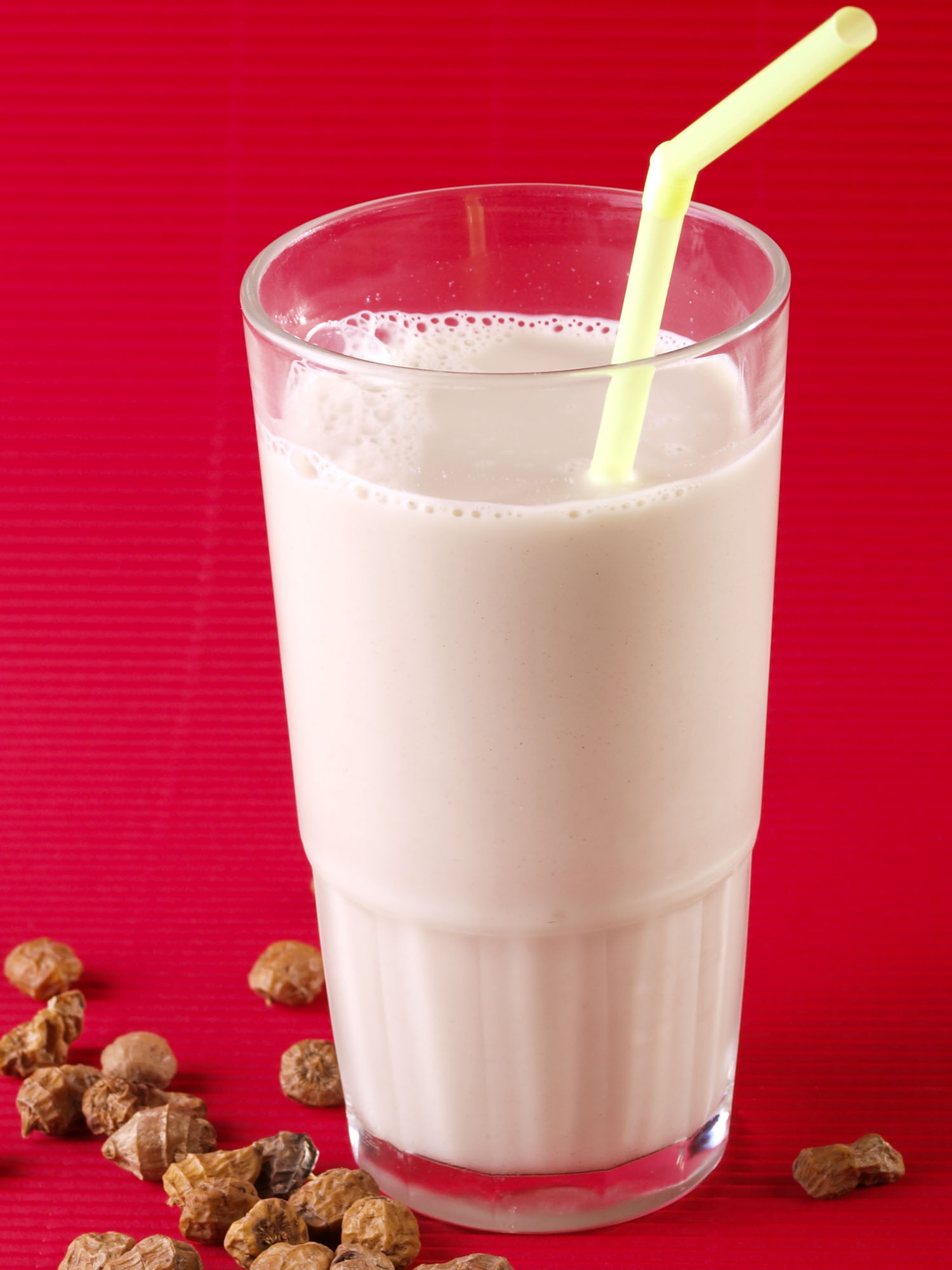 Horchata on a red background with a straw