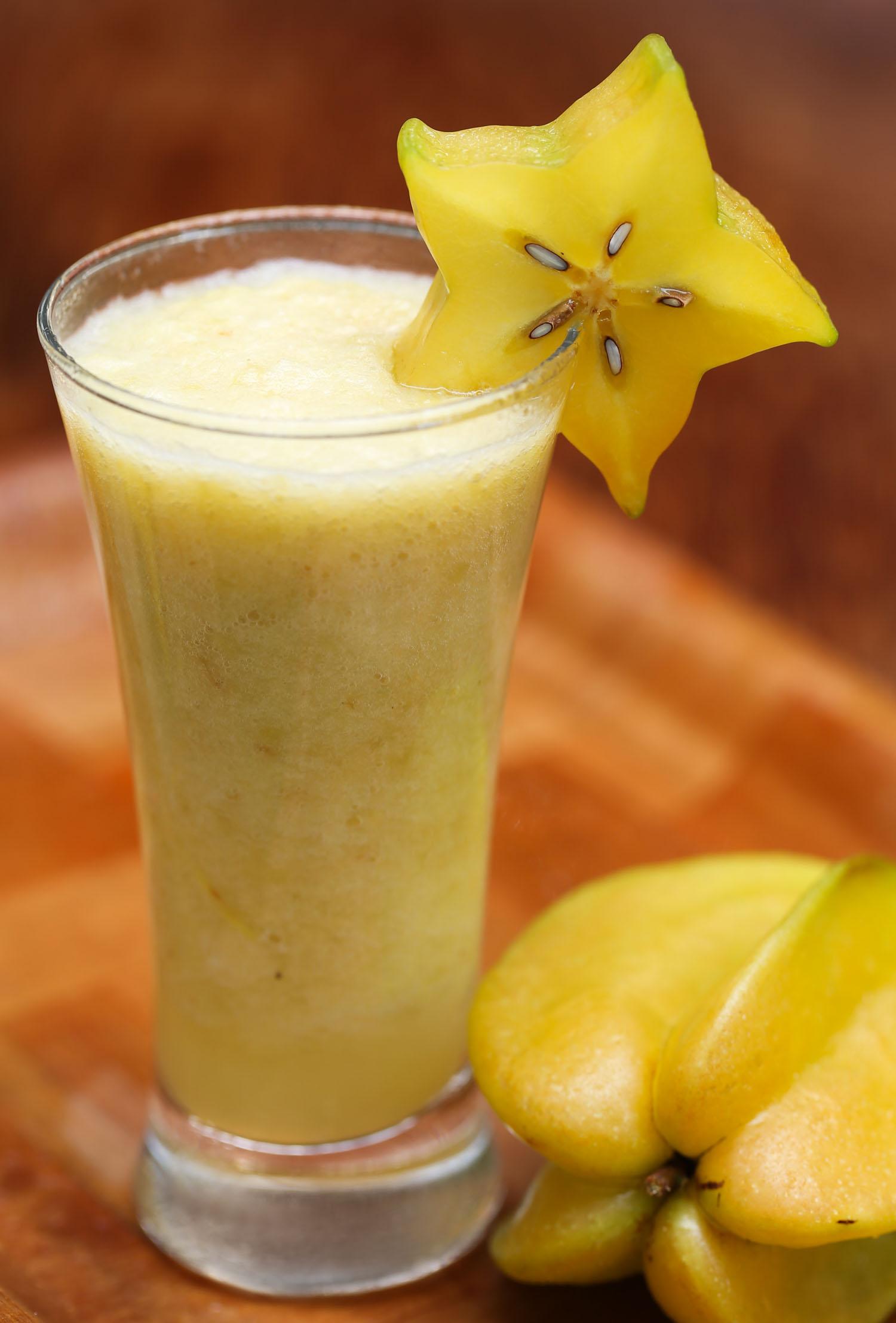 Carambolaor starfruit juice in a glass with ripe fruit known as licuado juice in Honduras