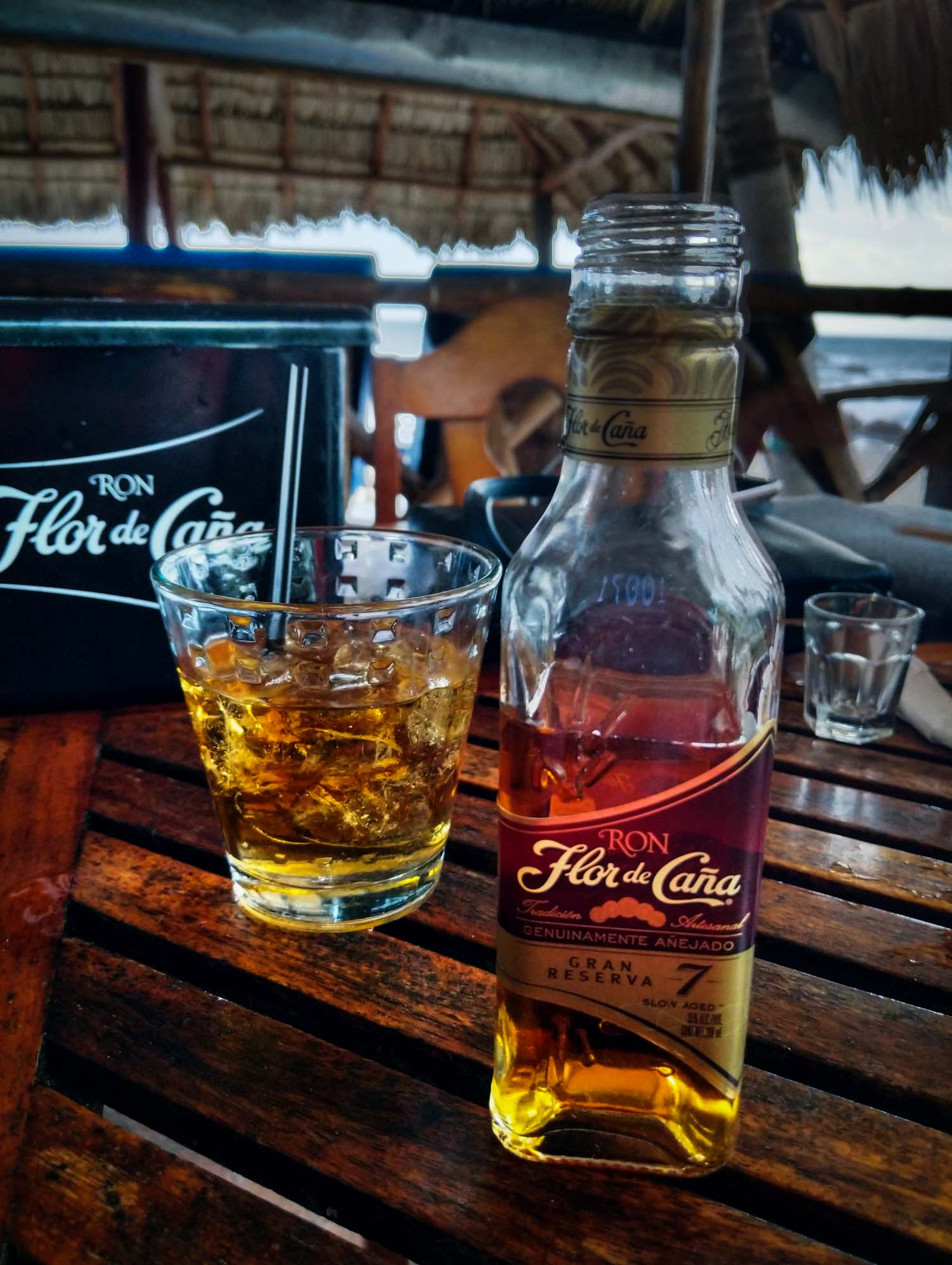 Bottle of Flor de Cana rum on a table with a glass behind it