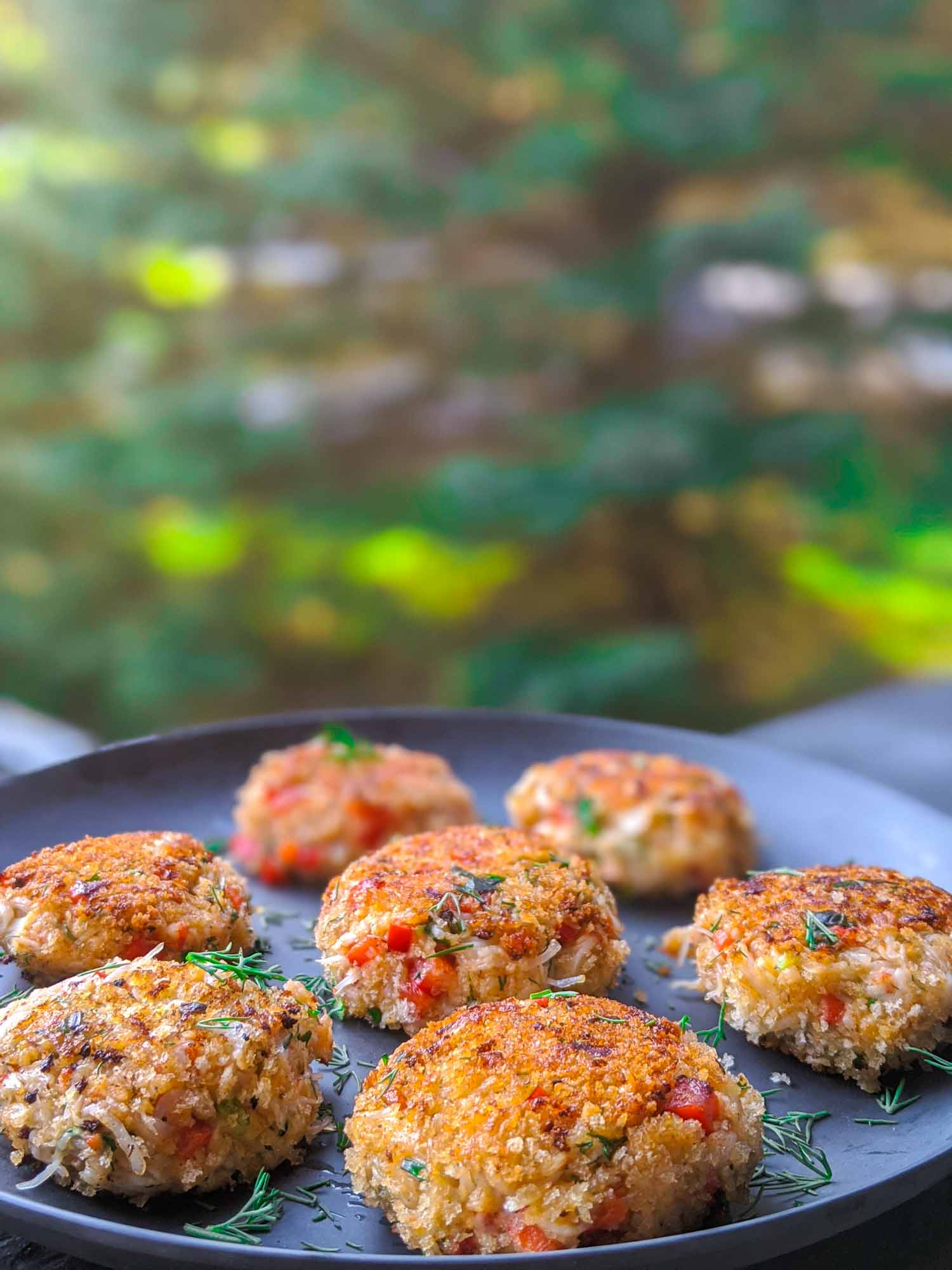 Snow crab cakes on a blue plate with trees in the background