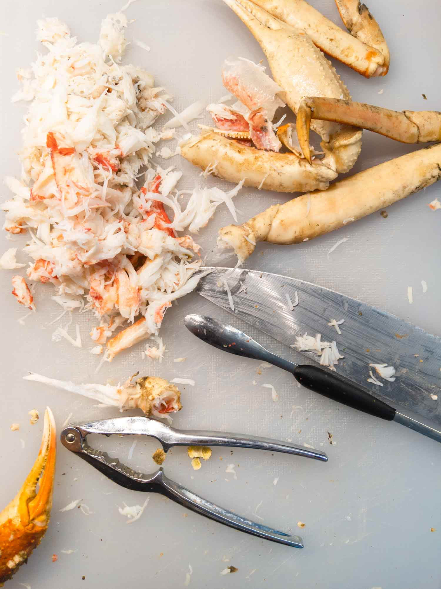 snow crab claws and meat on a white cutting board with a knife and cracker
