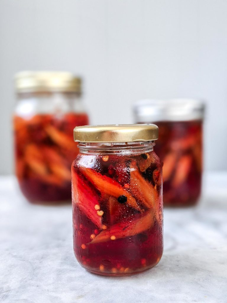 Three jars of rhubarb pickles, one in focus on marble countertop