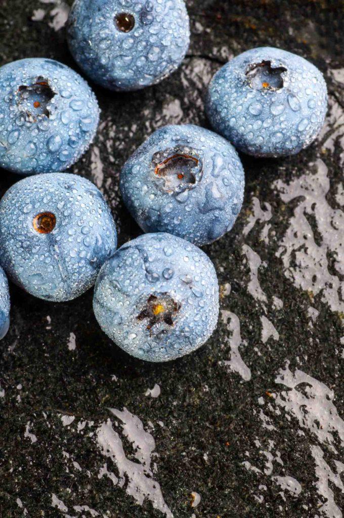 wet blueberries on black stone