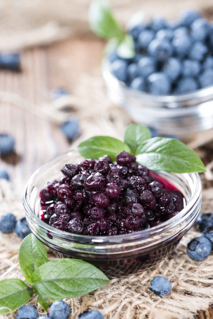 Portion of canned Blueberries on wooden background (close-up shot)