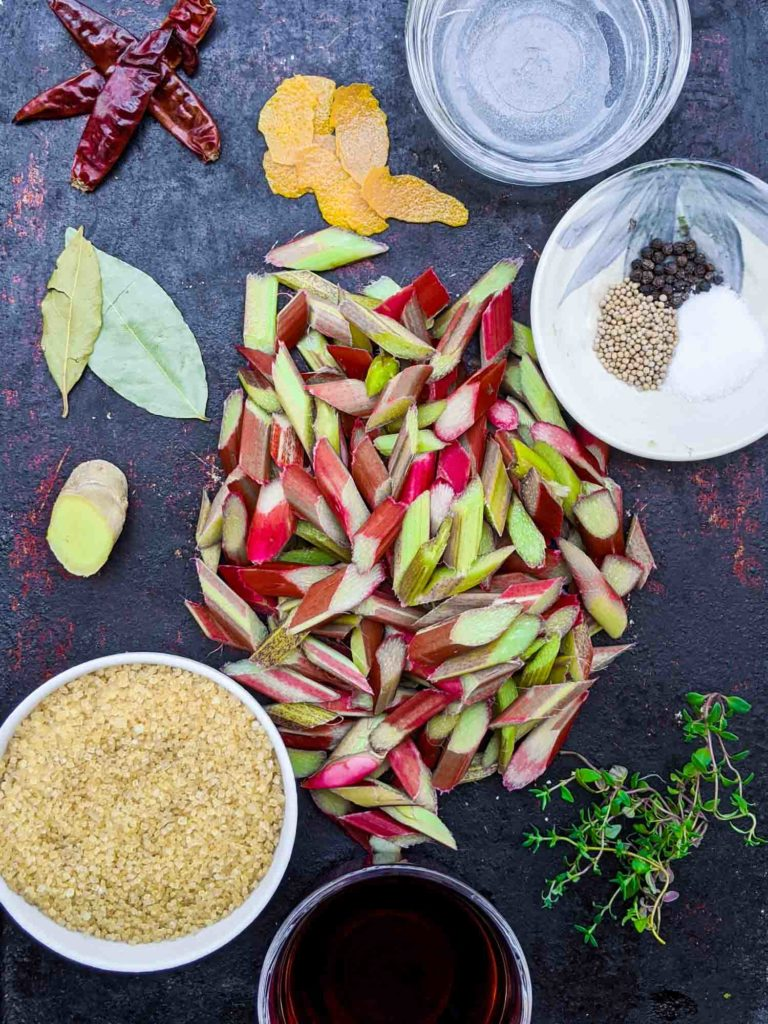 Ingredients for spicy pickled rhubarb on a baking sheet including turbinado sugar, ginger, bay leaves, dried chili peppers, orange peel, pepper, mustard seeds, sea salt, fresh type and red wine vinegar
