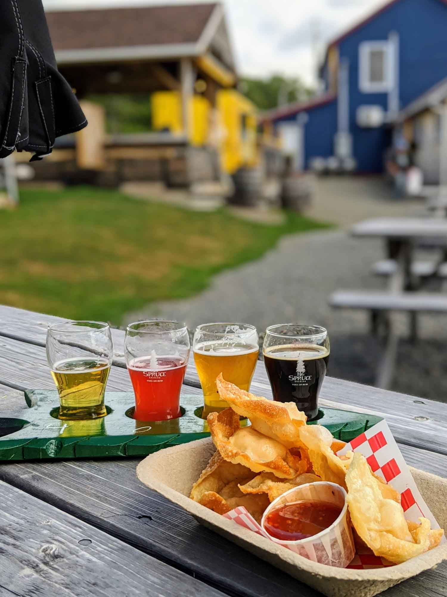 Big Spruce Brewing Company grounds with picnic tables. Flight of craft beer and lobster wontons