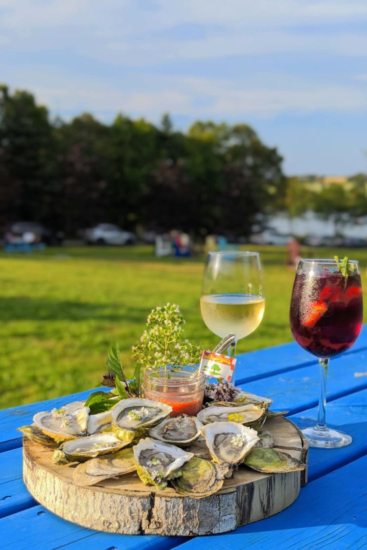 Oysters on a wooden trunk on a blue table with white wine and sangria