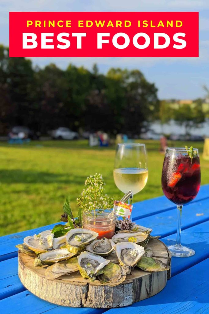 oysters on a blue picnic table with a glass of wine and a glass of sangria