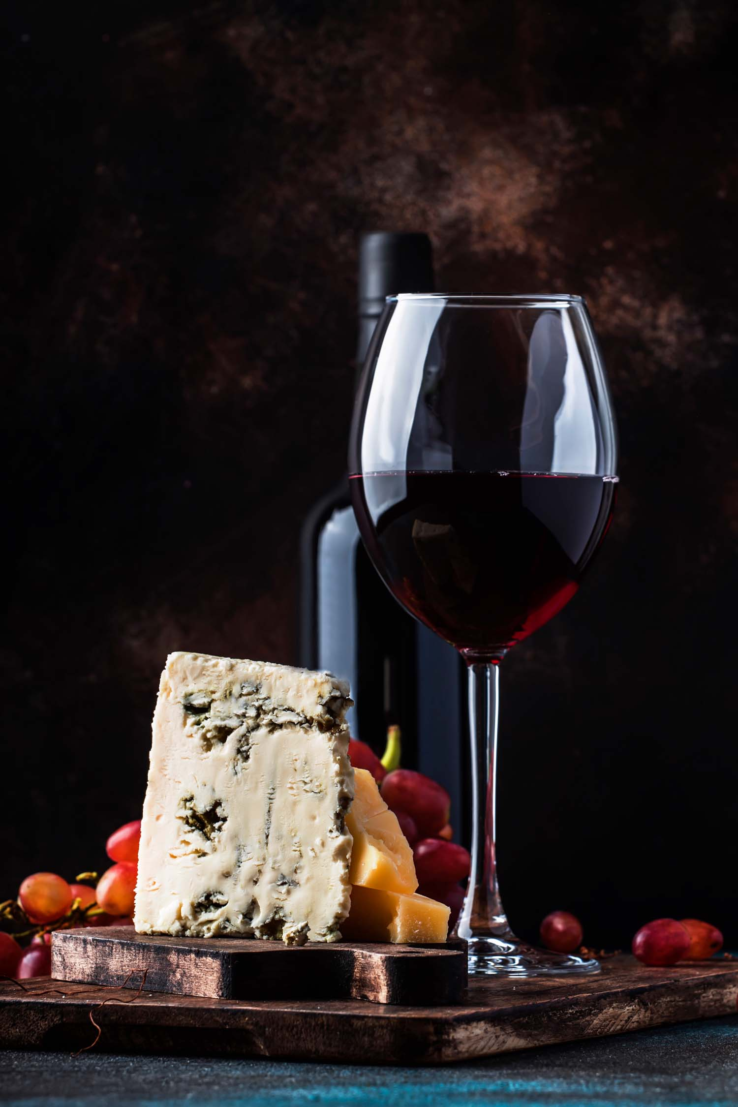 glass of port wine next to cheese fruit and nuts