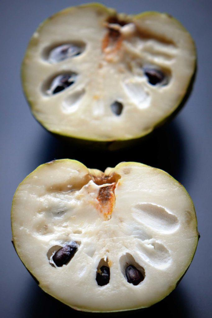 Custard apple cut open on black background