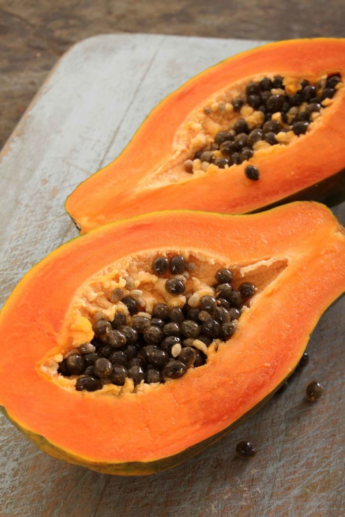 ripe papaya fruit in the Philippines cut open on a wooden board