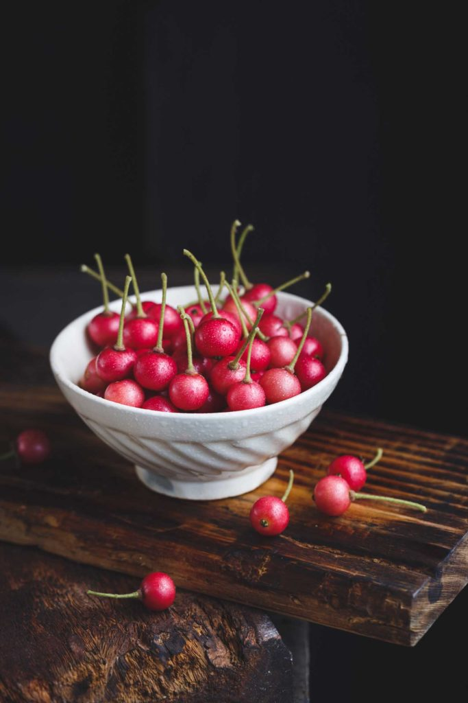 Panama cherry also called Jamaican cherry in a white bowl on a dark background