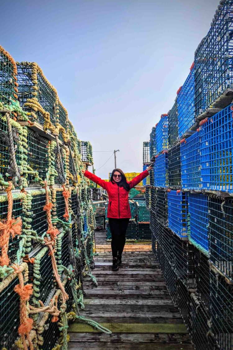 Ayngelina in red coat standing between lobster traps at Tusket Island Tours