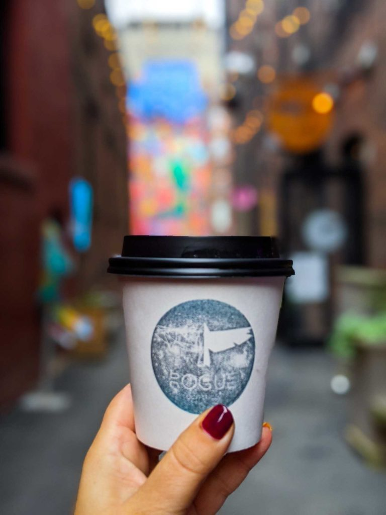 Coffee in hand in Rogue Alley Saint John