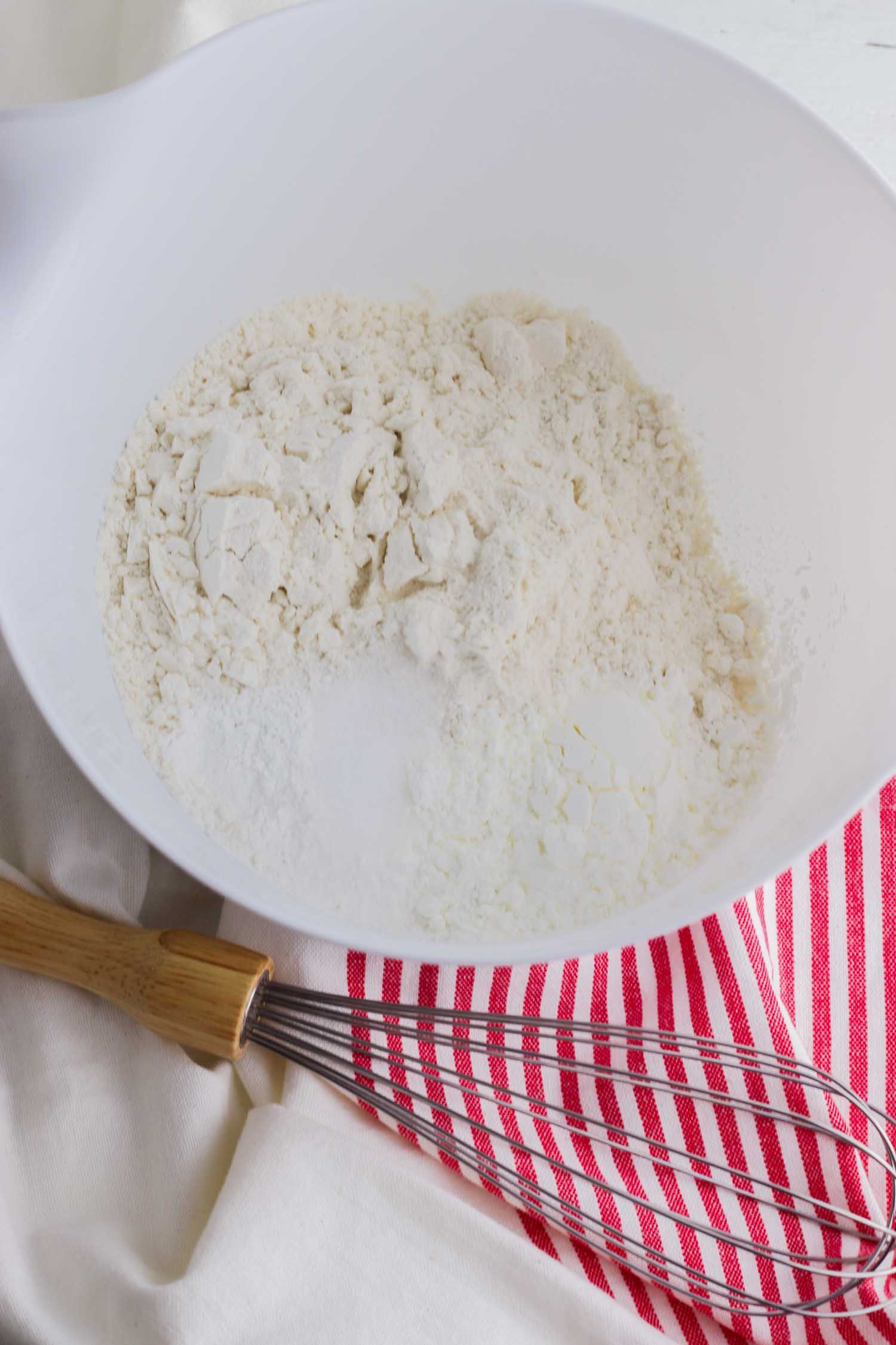flour in a white bowl with whisk and red and white tea towel