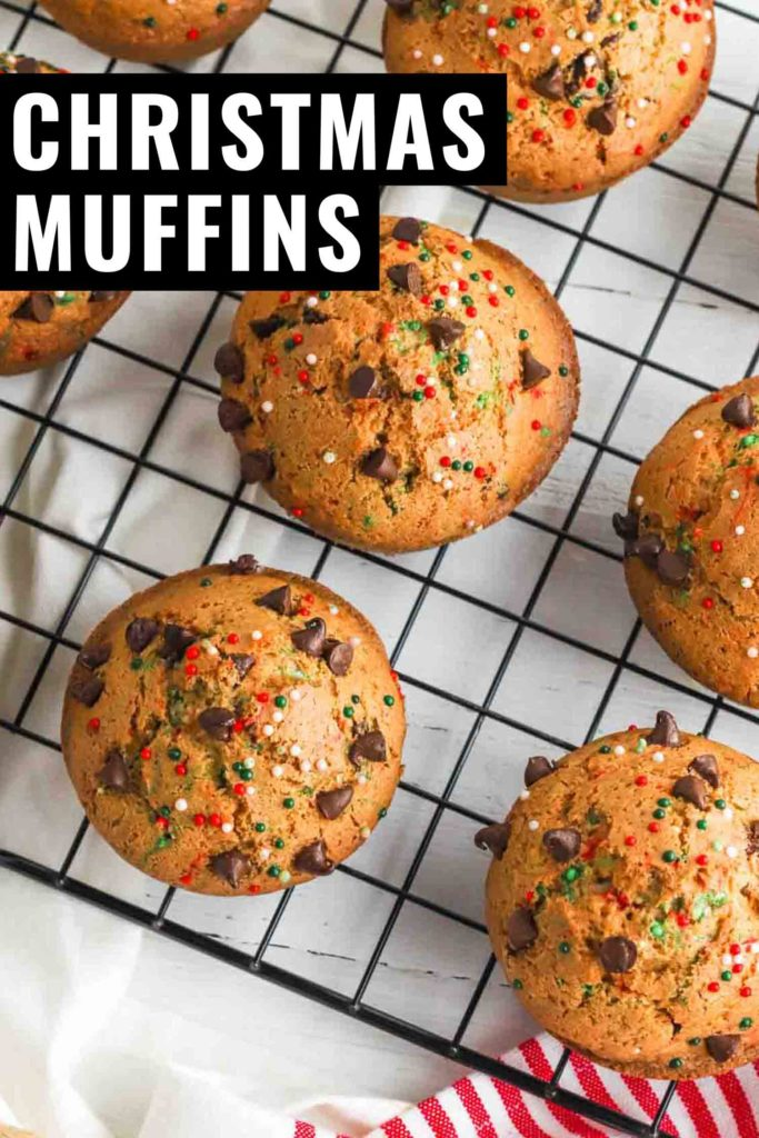 Holiday muffins with sprinkles on a cooling rack with whisk and red and white tea towel.