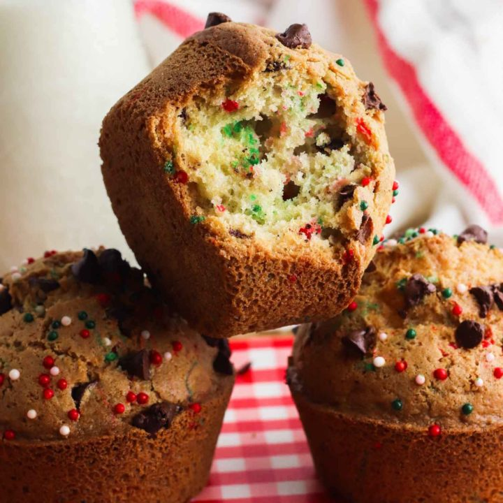 Christmas muffins stacked on red and white tablecloth with a bite out of one.