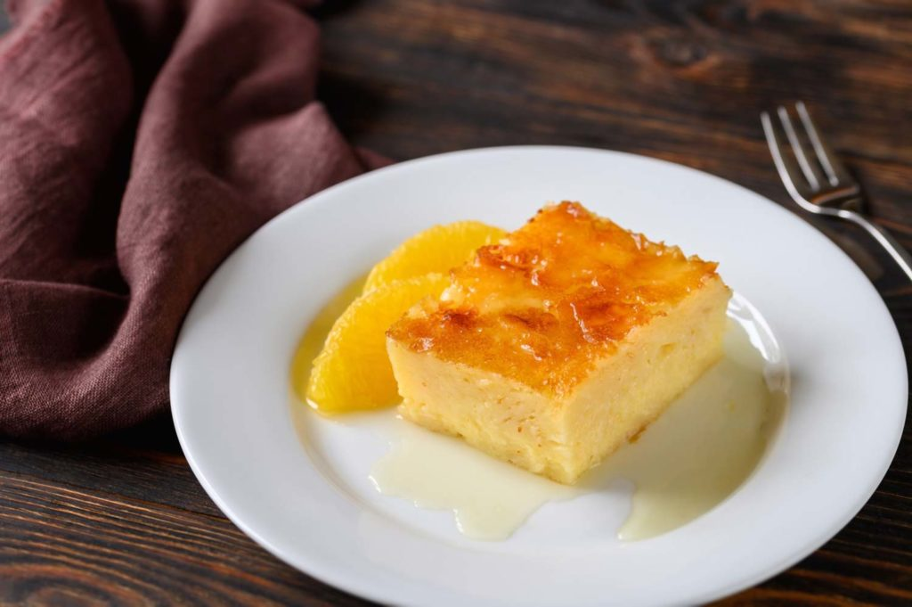 Dessert in Guatemala called borracho which is a sponge cake soaked in rum on a white plate garnished with orange