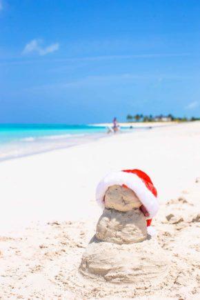 Little sandy snowman with red Santa Hat on white beach