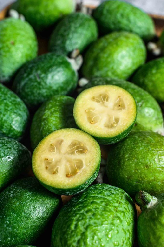Green feijoa on a wooden board. Gray background. Top view. Close up.