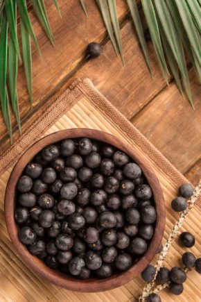 Brazilian fruits Acai berries in a bowl on a bamboo table with a palm leaf