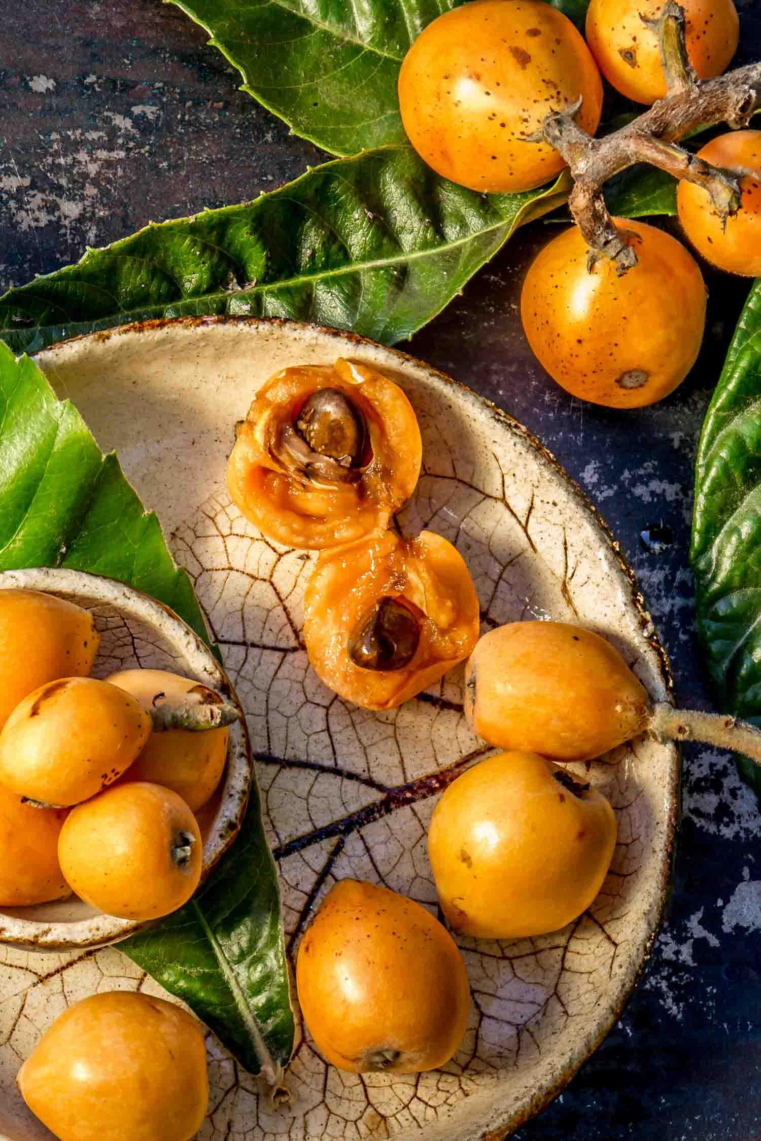 Loquat fruit. Nispero in Ecuador. Eriobotrya Japonica. Loquat with fresh leaves on metal background.