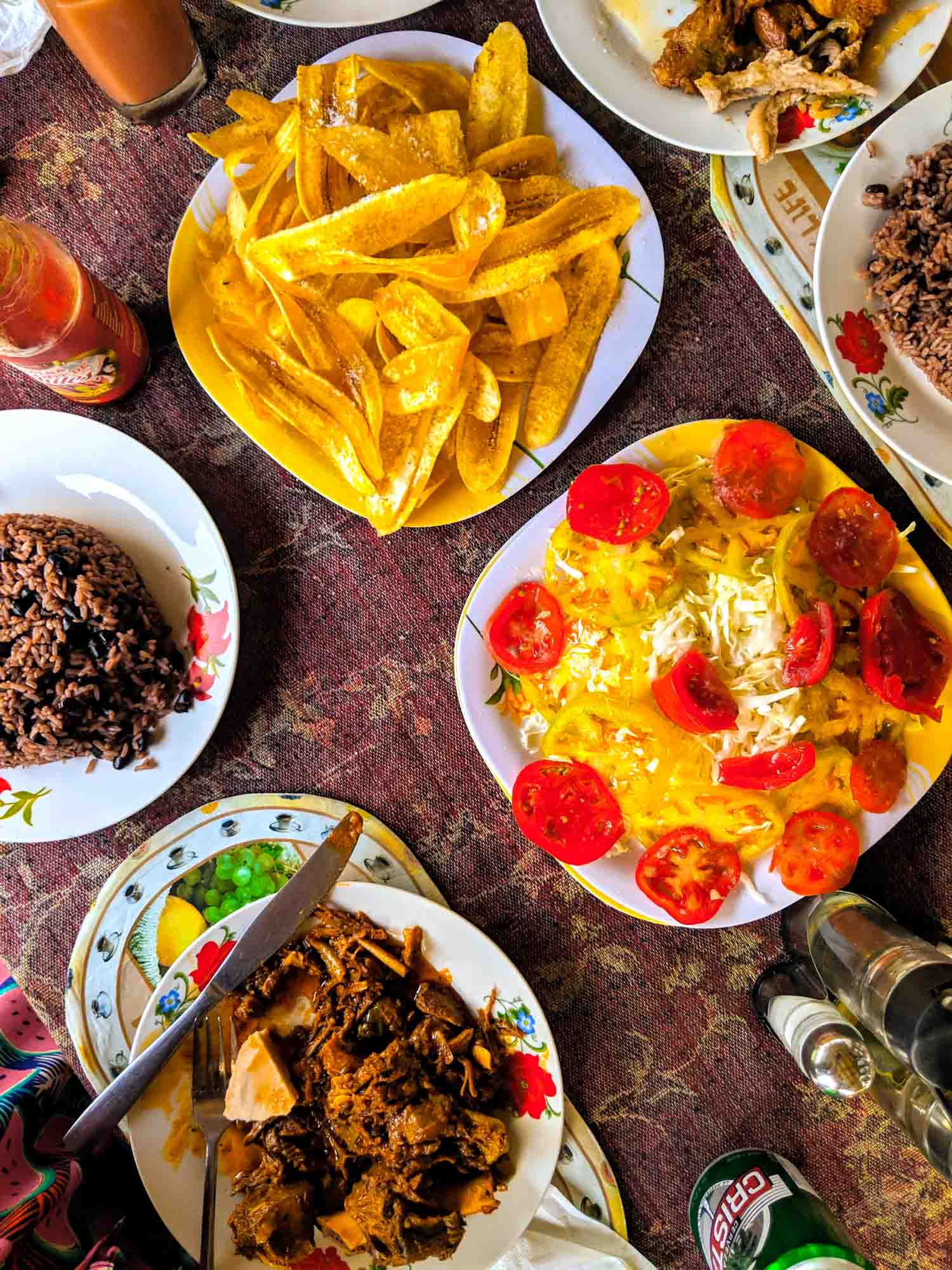 Typical countryside food at El Nicho, Cuba including plantains, cabbage, tomatoes, congri Cuban rice and stewed goat along with Cristal beer