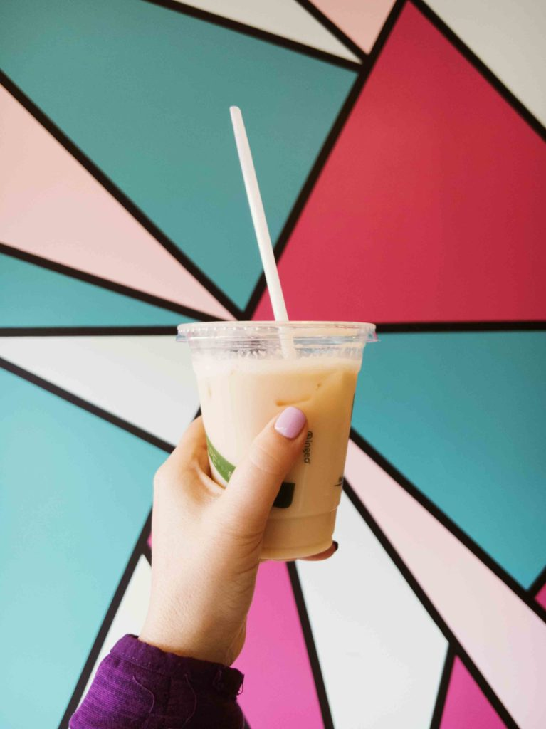 Rose Ice Tea Latte at Brew Beans with colourful background from interior