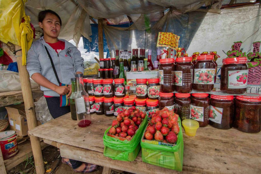 Market stand selling strawberry wine with vendor and strawberries on a table