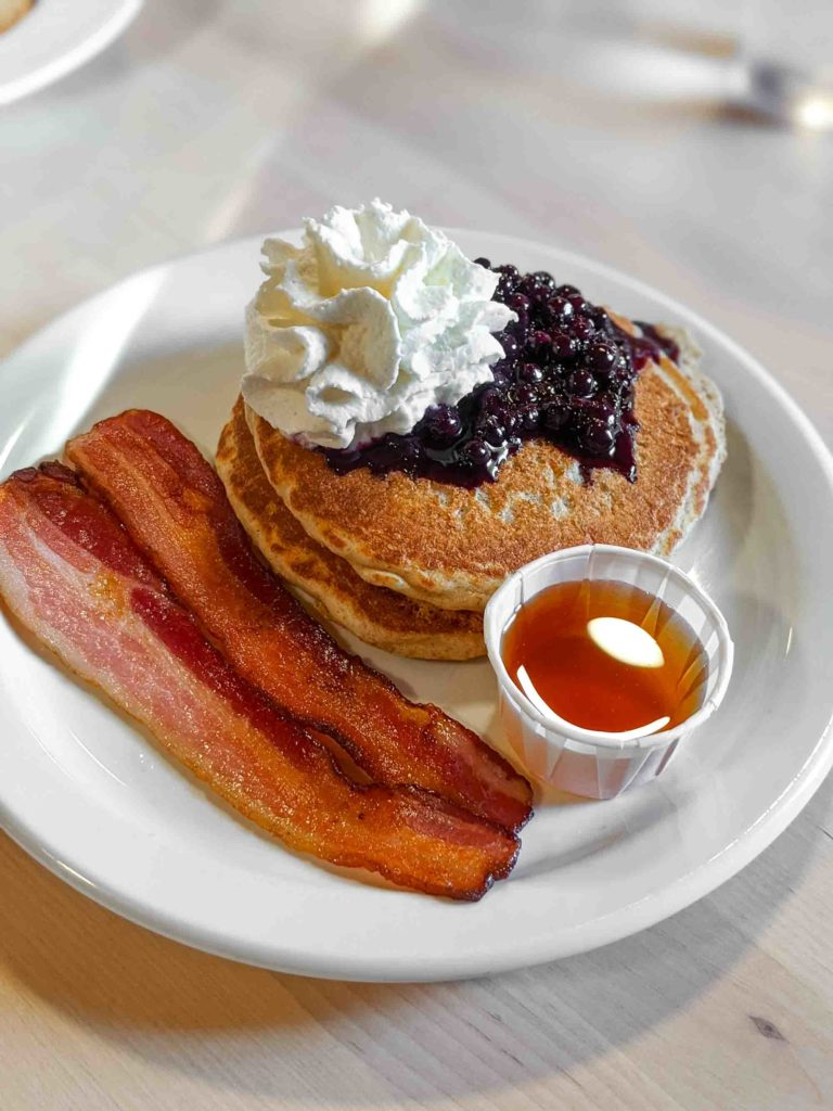 Pancakes with bacon and a side of maple syrup